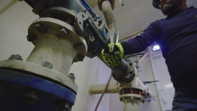 a male oilfield worker in his forties opens/closes valves to change the pressure of mud flow in a pump room at an oil and gas drilling pad site - oil industry stock videos & royalty-free footage