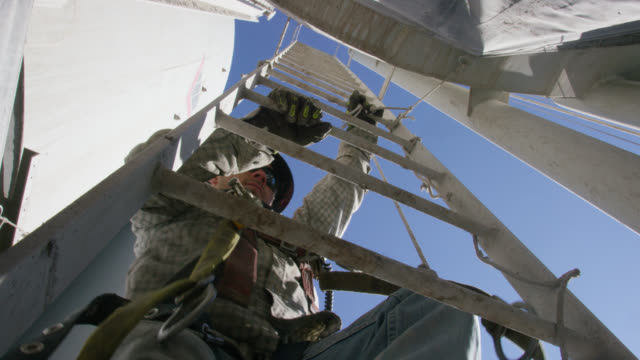 a male oilfield worker in his twenties attaches a safety cable to his harness and climbs a ladder on the side of a mud tank at an oil and gas drilling pad site on a sunny morning - safety harness stock videos & royalty-free footage