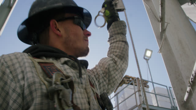 a male oilfield worker in his twenties checks the safety cable on a ladder on the side of a mud tank at an oil and gas drilling pad site on a sunny morning - oil industry stock videos & royalty-free footage