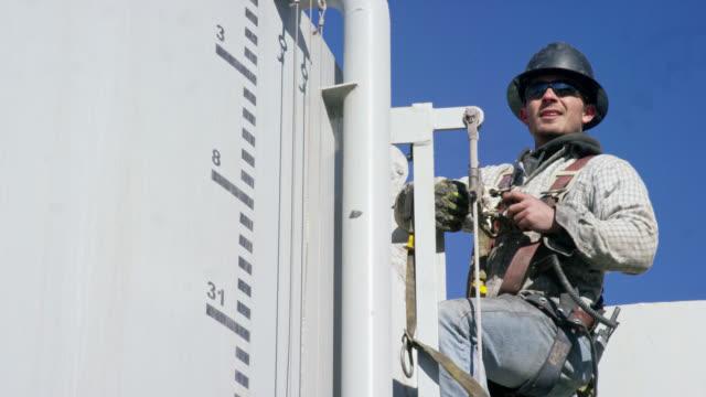 en manlig oljefält worker i tjugoårsåldern kommunicerar över en radio på en stege på sidan av en mud tank på en olja och gas drilling pad site på en solig morgon - stege bildbanksvideor och videomaterial från bakom kulisserna