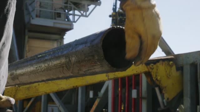 男性油田労働者は、晴れた朝に石油・ガス掘削パッドサイトでファイリングと溶接のためのパイプを準備します - 天然ガス点の映像素材/bロール