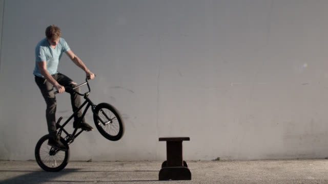 Male on bicycle performing jump trick