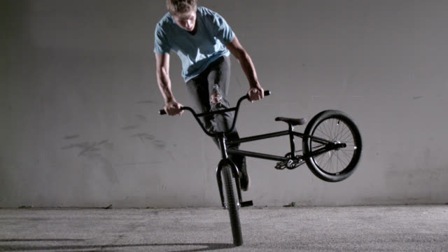 Male on bicycle performing tailwhip trick