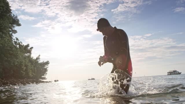 vídeos de stock e filmes b-roll de slo mo male open water swimmer exiting the water and checking the wrist watch - triatleta