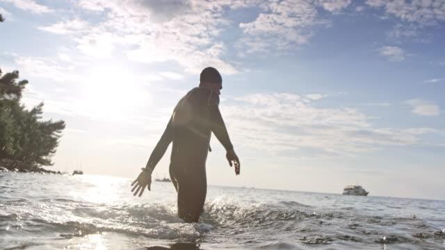 vídeos de stock e filmes b-roll de slo mo male open water swimmer staring from the beach in sunshine - triatleta
