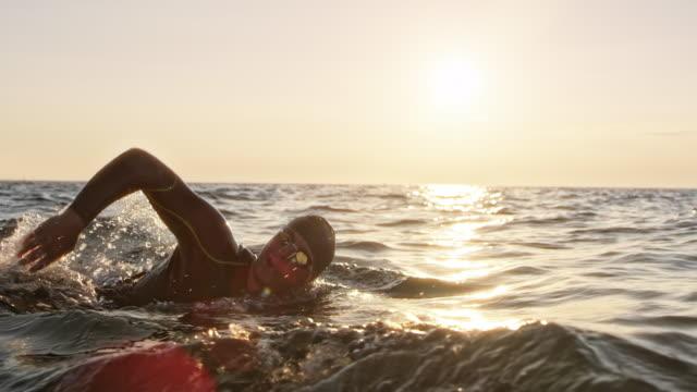 slo mo ts männlichen öffnen sie wasser-schwimmer schwimmen am aufgewühlte meer im sonnenschein - triathlet stock-videos und b-roll-filmmaterial