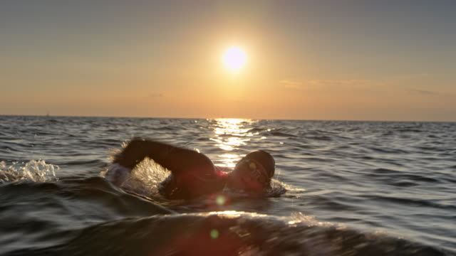 TS Male open water swimmer swimming forward crawl at sunset