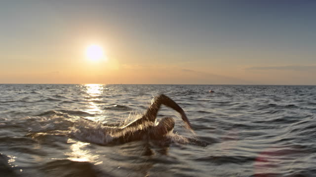 ts male open water swimmer swimming in choppy sea at sunset - swimming stock videos & royalty-free footage