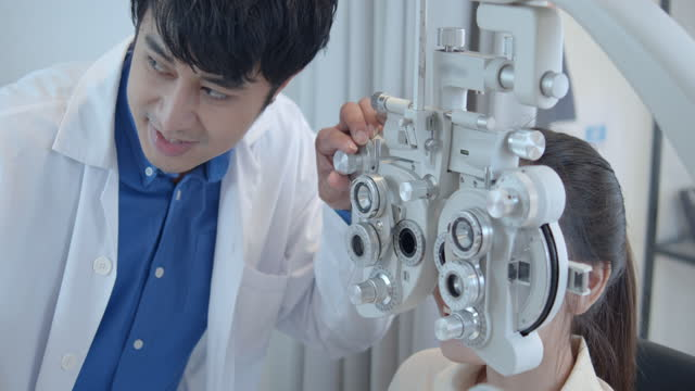 male optometrist checking female patient's eye sight with machine,4k footage from raw vdo - lens optical instrument stock videos & royalty-free footage