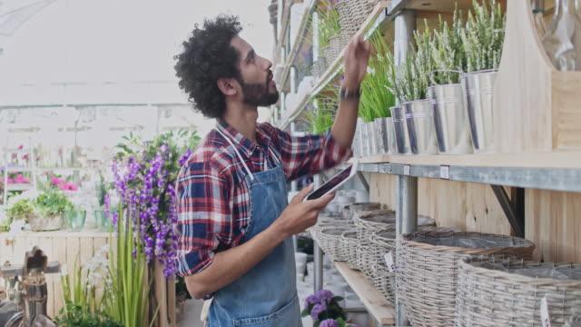 vídeos y material grabado en eventos de stock de hombre dueño uso tableta digital en el centro de jardín - colección