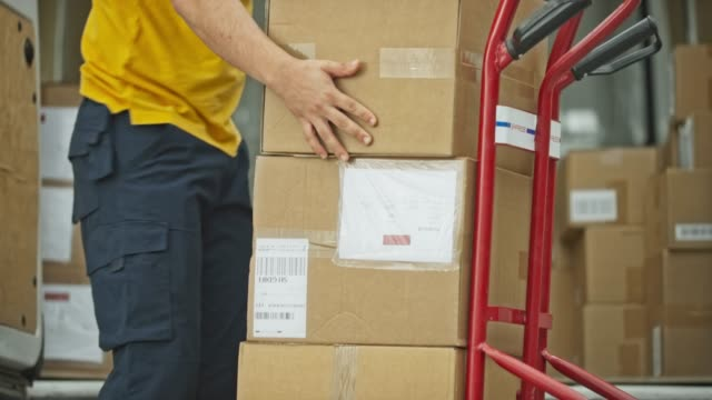 male package delivery service worker placing packages from the van onto the cart - van stock videos & royalty-free footage