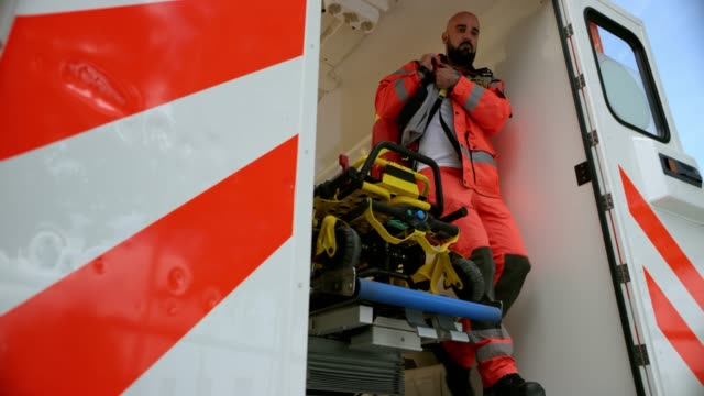 slo mo ds male paramedic carrying his paramedic bag and rushing out of the ambulance vehicle - slovenia stock videos & royalty-free footage