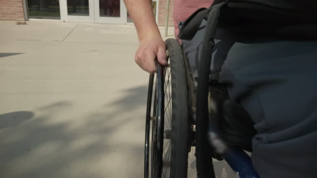 male paraplegic navigating in wheelchair outdoors on a sunny late summer day 4k video series - paraplegic stock videos & royalty-free footage
