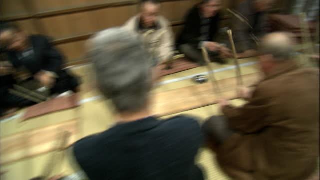 stockvideo's en b-roll-footage met male parishioners beat board simultaneously with wooden sticks, japan - in kleermakerszit