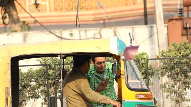 männlicher passagier und rikschafahrer im gespräch über buchung - rikscha stock-videos und b-roll-filmmaterial
