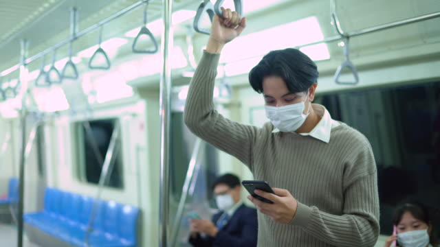 male passenger in metro train wearing face mask using his smart phone - public transport stock videos & royalty-free footage
