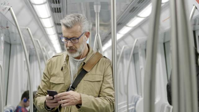 vidéos et rushes de musique d'écoute de passager mâle dans le train - passager