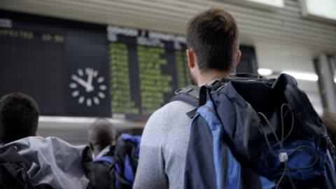 stockvideo's en b-roll-footage met mannelijke passagiers kijkend naar de vlucht informatie weer te geven op de luchthaven - rugzak
