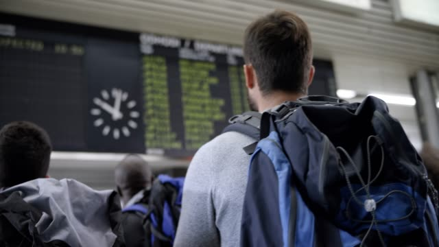 male passenger looking at the flight information display at the airport - zaino da montagna video stock e b–roll