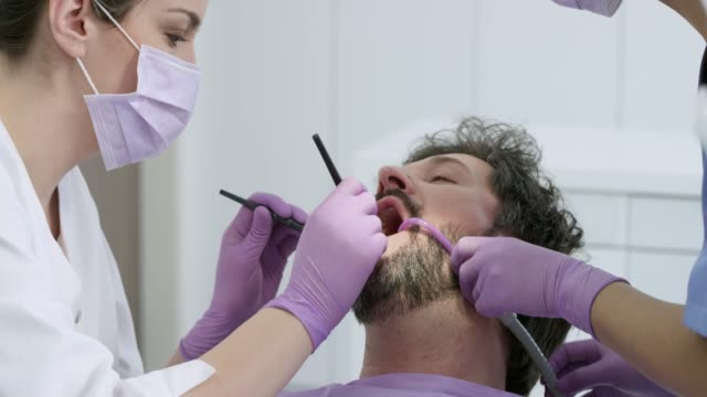 male patient getting his tooth repaired at the dentist's office - dentist stock videos & royalty-free footage