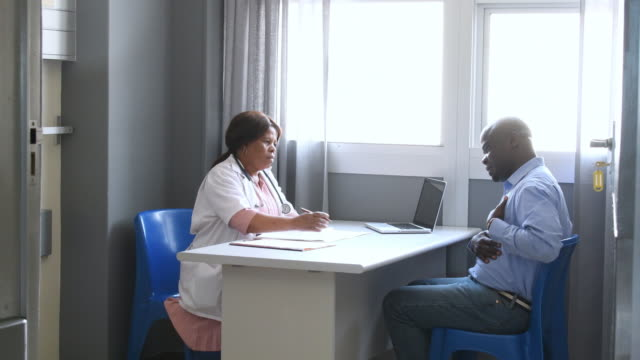 male patient meeting with mature female doctor - south africa stock videos & royalty-free footage