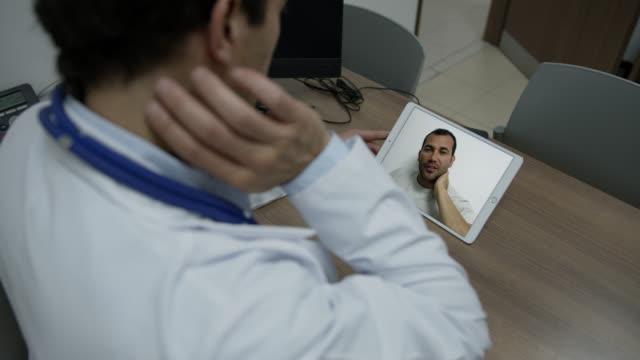 vídeos y material grabado en eventos de stock de paciente masculino en una videoconferencia con el médico quejándose del dolor mientras está en estado de bloqueo de emergencia - dolor