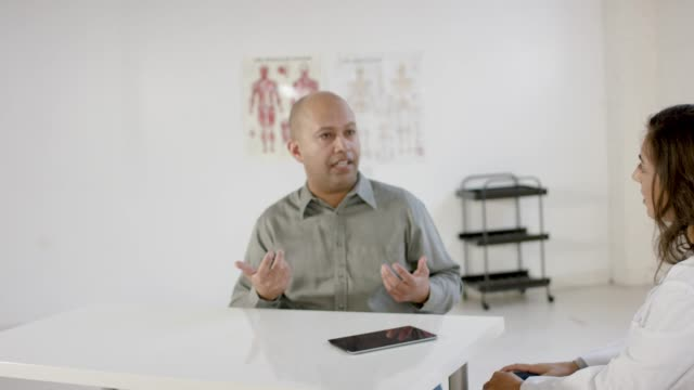 male patient seeks advice from medical professional in consultation - nutritionist stock videos and b-roll footage
