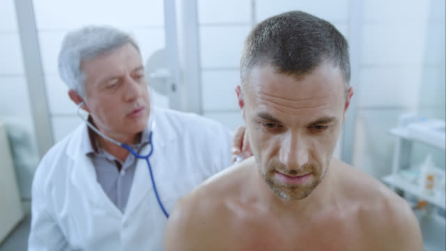 Male patients face while having an auscultation examination by doctor