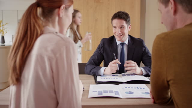 Male personal banker visiting couple at home for a consultation