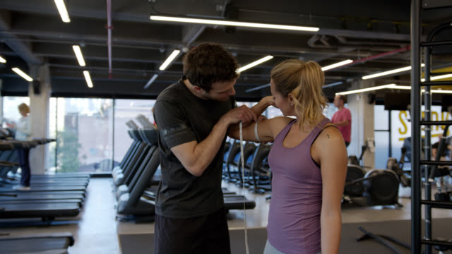 male personal coach measuring arms and waist of young woman who has been training at the gym - thin stock videos & royalty-free footage