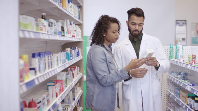 male pharmacist assists woman in pharmacy - males stock videos & royalty-free footage