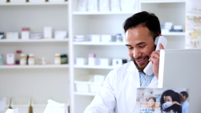male pharmacist talks with customer on the phone - doctor multitasking stock videos & royalty-free footage