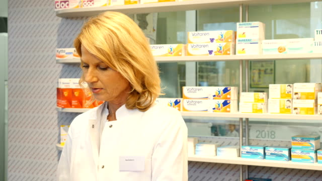 vídeos de stock e filmes b-roll de male pharmacist using computer at checkout counter - one mature woman only