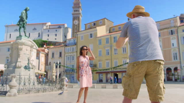 male photographer directing a female model while taking photos in the square of a coastal town - slovenia stock videos & royalty-free footage