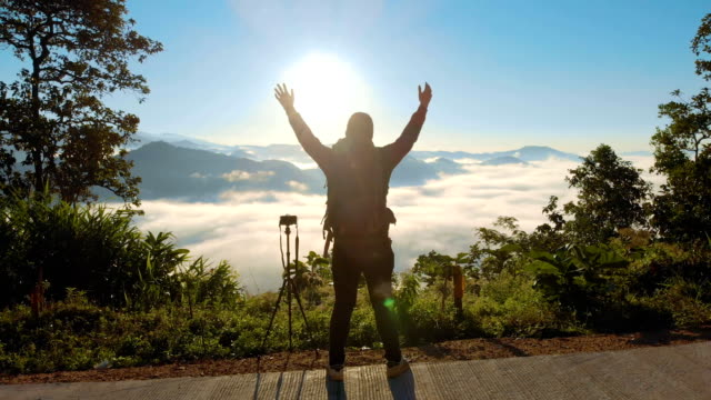 aerial male photographer standing on the mountain and raising his hands in morning sunrise - photographer stock videos & royalty-free footage