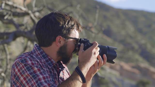 男性カメラマンが荒野で写真をとる - デジタル一眼レフカメラ点の映像素材/bロール