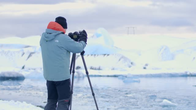 ms male photographer with camera and tripod photographing glacier,iceland - professione creativa video stock e b–roll