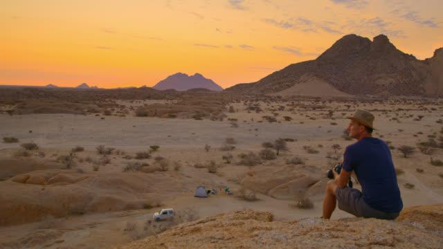 vidéos et rushes de ws photographe masculin avec l'appareil-photo regardant les pics pittoresques de spitzkoppe, namibie, afrique - prendre une photo