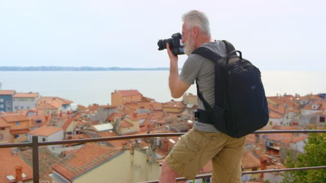 灰色の髪とひげ彼の下の絵のような海岸沿い町の写真を撮る男性カメラマン - one mature man only点の映像素材/bロール