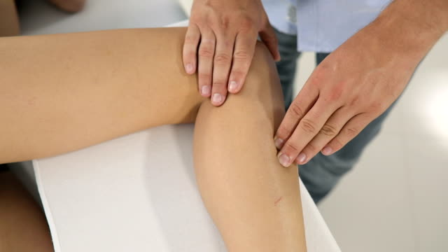 male physiotherapist giving leg massage to female patient - human leg stock videos & royalty-free footage