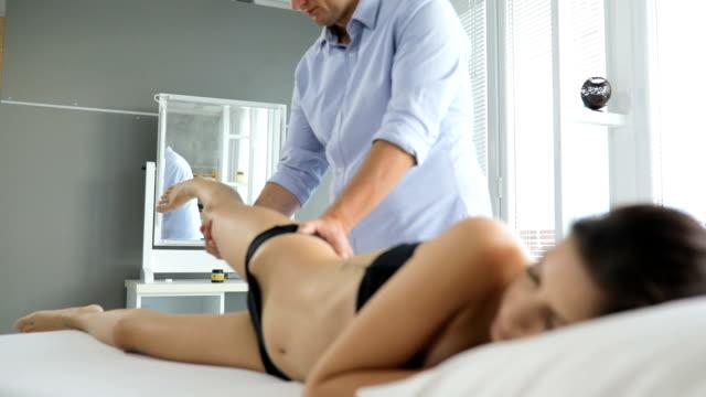 vídeos de stock, filmes e b-roll de perna dando fisioterapeuta masculino massagem para paciente do sexo feminino - fisioterapeuta