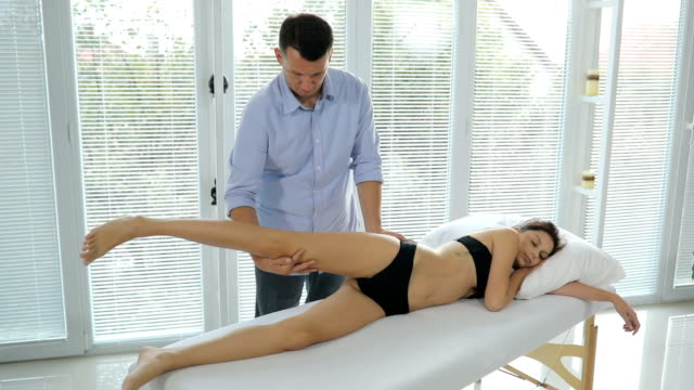 Male physiotherapist giving leg massage to female patient