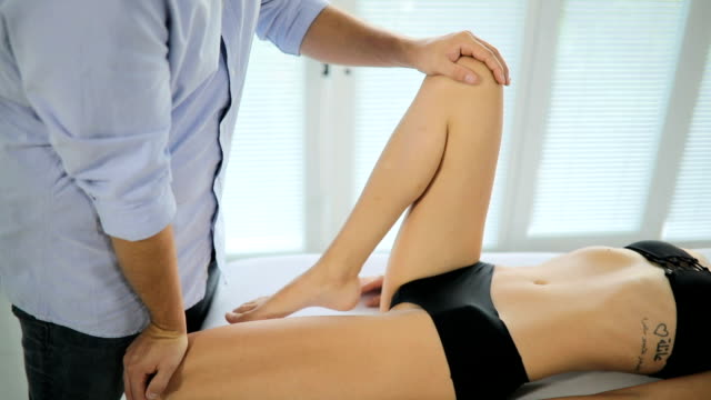 male physiotherapist giving leg massage to female patient - inginocchiarsi video stock e b–roll