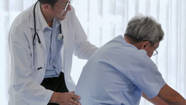 Male physiotherapist working on back of senior male patient with injury.Physiotherapist working with patient in clinic.Healthcare: Caretaking concept.Rehabilitation physiotherapy concept.