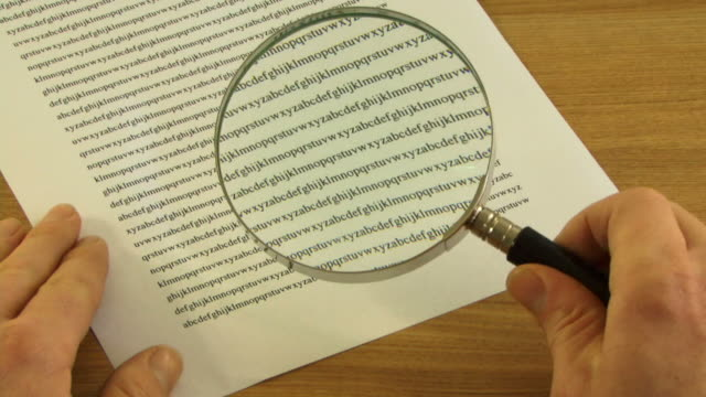 vídeos de stock e filmes b-roll de male picking up magnifying glass to look at small print in contract - contrato