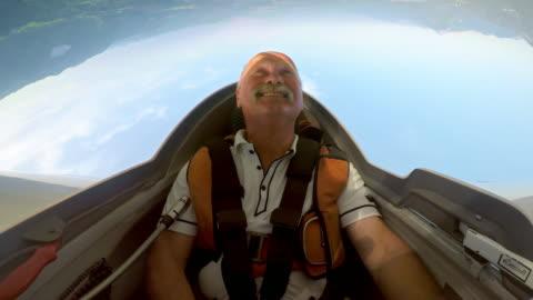 vidéos et rushes de pilote de ld mâle faisant des cascades sur une journée ensoleillée à son planeur - pilote