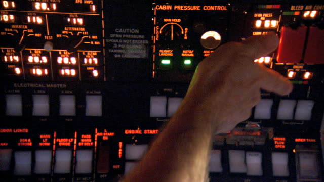 male pilot fingers pushing buttons on cockpit overhead panel, hand pulling flap lever below throttle next to copilot sitting w/ manual on lap. - throttle stock videos & royalty-free footage