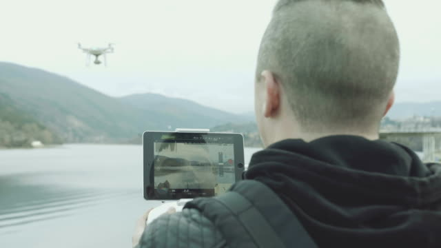 male pilot flying his drone over beautiful lake in slow motion - piloting stock videos and b-roll footage