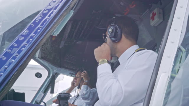 a male pilot of latin ethnicity with a female pilot of caucasian ethnicity prepares in the cabin before the plane takes off. - crew stock videos & royalty-free footage