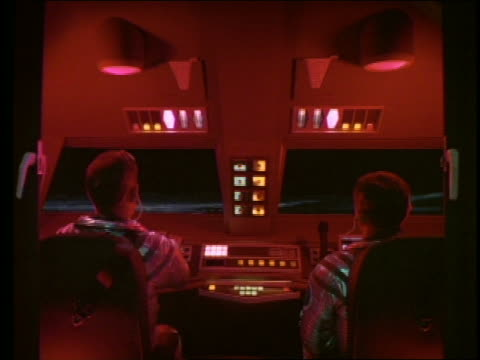2 male pilots in red-lit cockpit of moon bus